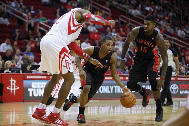 Nov 11, 2013; Houston, TX, USA; Toronto Raptors point guard Kyle Lowry (7) drives around Houston Rockets center Dwight Howard (12) during the second overtime period at Toyota Center. Mandatory Credit: Andrew Richardson-USA TODAY Sports