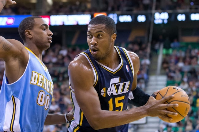 Nov 11, 2013; Salt Lake City, UT, USA; Utah Jazz power forward Derrick Favors (15) is defended by Denver Nuggets power forward Darrell Arthur (00) during the second half at EnergySolutions Arena. Denver won 100-81. Mandatory Credit: Russ Isabella-USA TODAY Sports