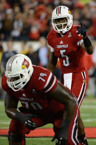 Oct 10, 2013; Louisville, KY, USA; Louisville Cardinals quarterback Teddy Bridgewater (5) adjusts a play at the line of scrimmage during the second half of play against the Rutgers Scarlet Knights at Papa John's Cardinal Stadium. Mandatory Credit: Jamie Rhodes-USA TODAY Sports
