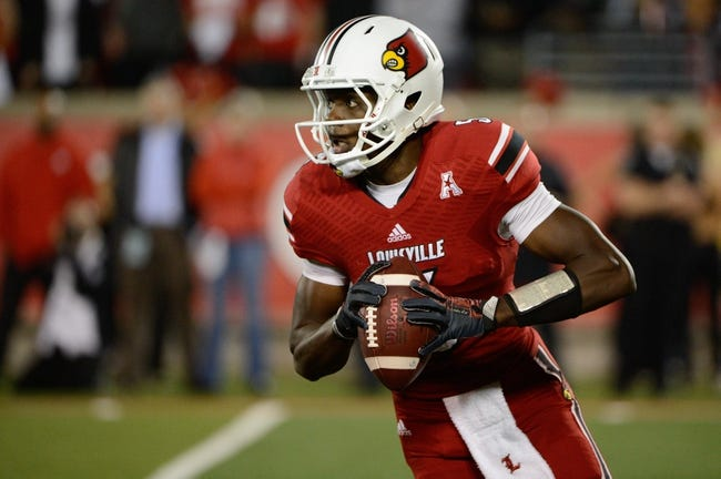 Oct 10, 2013; Louisville, KY, USA; Louisville Cardinals quarterback Teddy Bridgewater (5) scrambles with the ball during the second half against the Rutgers Scarlet Knights  at Papa John's Cardinal Stadium. Mandatory Credit: Jamie Rhodes-USA TODAY Sports