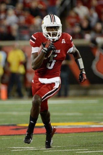 Oct 10, 2013; Louisville, KY, USA; Louisville Cardinals quarterback Teddy Bridgewater (5) runs the ball against the Rutgers Scarlet Knights during the first quarter of play at Papa John's Cardinal Stadium. Mandatory Credit: Jamie Rhodes-USA TODAY Sports