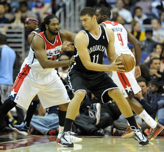 Nov 8, 2013; Washington, DC, USA; Washington Wizards power forward Nene Hilario (42) defends Brooklyn Nets center Brook Lopez (11) during the first half at the Verizon Center. Mandatory Credit: Brad Mills-USA TODAY Sports