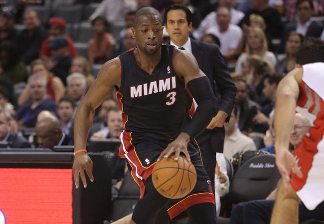 Nov 5, 2013; Toronto, Ontario, CAN; Miami Heat guard Dwyane Wade (3) dribbles as he is watched by head coach Erik Spoelstra behind him against the Toronto Raptors at Air Canada Centre. The Heat beat the Raptors 104-95. Mandatory Credit: Tom Szczerbowski-USA TODAY Sports