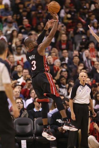 Nov 5, 2013; Toronto, Ontario, CAN; Miami Heat guard Dwyane Wade (3) shoots against the Toronto Raptors at Air Canada Centre. The Heat beat the Raptors 104-95. Mandatory Credit: Tom Szczerbowski-USA TODAY Sports