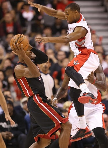 Nov 5, 2013; Toronto, Ontario, CAN; Toronto Raptors point guard Kyle Lowry (7) defends against Miami Heat guard Ray Allen (34) at Air Canada Centre. The Heat beat the Raptors 104-95. Mandatory Credit: Tom Szczerbowski-USA TODAY Sports