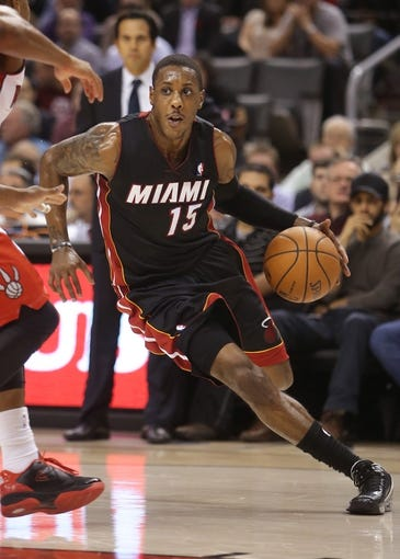 Nov 5, 2013; Toronto, Ontario, CAN; Miami Heat point guard Mario Chalmers (15) drives to the basket against the Toronto Raptors at Air Canada Centre. The Heat beat the Raptors 104-95. Mandatory Credit: Tom Szczerbowski-USA TODAY Sports