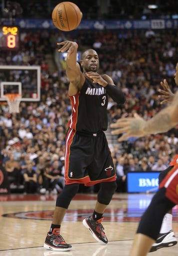 Nov 5, 2013; Toronto, Ontario, CAN; Miami Heat guard Dwyane Wade (3) passes the ball against the Toronto Raptors at Air Canada Centre. The Heat beat the Raptors 104-95. Mandatory Credit: Tom Szczerbowski-USA TODAY Sports
