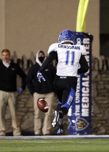 Nov 12, 2013; Toledo, OH, USA; Buffalo Bulls punter Tyler Grassman (11) runs after a high snap that flew over his head during the second quarter against the Toledo Rockets at Glass Bowl. Mandatory Credit: Raj Mehta-USA TODAY Sports