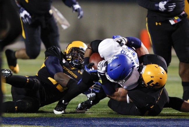 Nov 12, 2013; Toledo, OH, USA; Buffalo Bulls running back Anthone Taylor (14) gets tackled by Toledo Rockets defensive back Junior Sylvestre (left) and linebacker Chase Murdock (40) during the fourth quarter at Glass Bowl. The Rockets beat the Bulls 51-41. Mandatory Credit: Raj Mehta-USA TODAY Sports