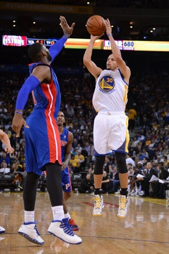 November 12, 2013; Oakland, CA, USA; Golden State Warriors point guard Stephen Curry (30) shoots the ball against Detroit Pistons center Andre Drummond (0, left) during the third quarter at Oracle Arena. The Warriors defeated the Pistons 113-95. Mandatory Credit: Kyle Terada-USA TODAY Sports