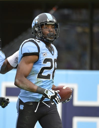 Nov 9, 2013; Chapel Hill, NC, USA; North Carolina Tar Heels defensive back Dominique Green (26) celebrates after returning an interception for a touchdown in the third quarter. The Tar Heels defeated the Cavaliers 45-14 at Kenan Memorial Stadium. Mandatory Credit: Bob Donnan-USA TODAY Sports