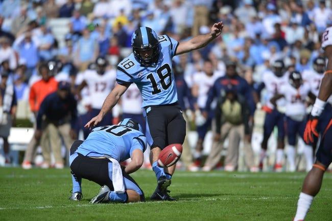 Nov 9, 2013; Chapel Hill, NC, USA; North Carolina Tar Heels kicker Thomas Moore (18) kicks a field goal as punter Tommy Hibbard (30) holds in the first quarter at Kenan Memorial Stadium. Mandatory Credit: Bob Donnan-USA TODAY Sports