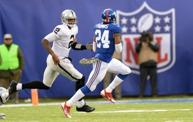 Nov 10, 2013; East Rutherford, NJ, USA; New York Giants cornerback Terrell Thomas (24) is pursued by Oakland Raiders quarterback Terrelle Pryor (2) on a 65-yard interception return at MetLife Stadium. The Giants defeated the Raiders 24-20. Mandatory Credit: Kirby Lee-USA TODAY Sports