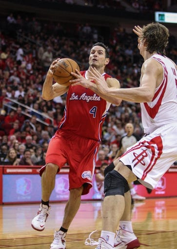 Nov 9, 2013; Houston, TX, USA; Los Angeles Clippers shooting guard J.J. Redick (4) drives the ball during the third quarter as Houston Rockets center Omer Asik (3) defends at Toyota Center. Mandatory Credit: Troy Taormina-USA TODAY Sports