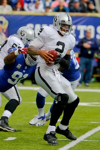 Nov 10, 2013; East Rutherford, NJ, USA;  New York Giants defensive end Justin Tuck (91) tackles Oakland Raiders quarterback Terrelle Pryor (2) during the first half at MetLife Stadium. Mandatory Credit: Jim O'Connor-USA TODAY Sports