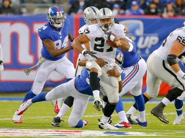 Nov 10, 2013; East Rutherford, NJ, USA;  Oakland Raiders running back Rashad Jennings (27) tries to get away from New York Giants outside linebacker Keith Rivers (55) during the first half at MetLife Stadium. Mandatory Credit: Jim O'Connor-USA TODAY Sports