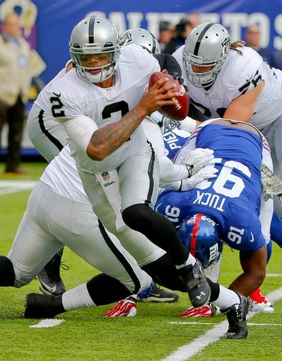 Nov 10, 2013; East Rutherford, NJ, USA;  New York Giants defensive end Justin Tuck (91) puts pressure on Oakland Raiders quarterback Terrelle Pryor (2) during the first half at MetLife Stadium. Mandatory Credit: Jim O'Connor-USA TODAY Sports
