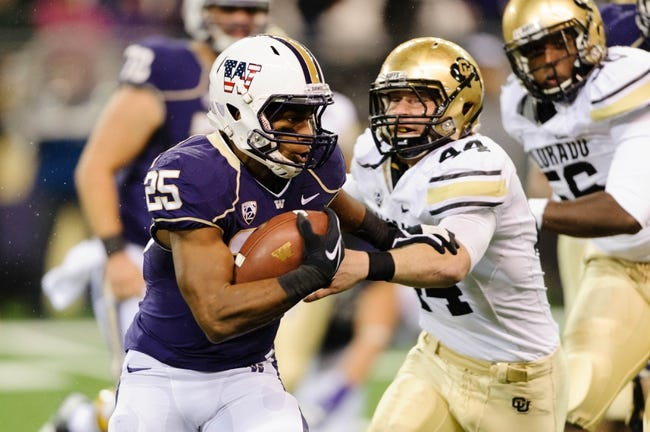 Nov 9, 2013; Seattle, WA, USA; Washington Huskies running back Bishop Sankey (25) stiff arms Colorado Buffaloes linebacker Addison Gillam (44) during the game at Husky Stadium. Washington defeated Colorado 59-7. Mandatory Credit: Steven Bisig-USA TODAY Sports