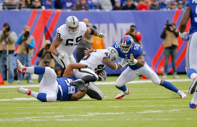 Nov 10, 2013; East Rutherford, NJ, USA;  Oakland Raiders fullback Marcel Reece (45) is wrapped up by New York Giants defensive tackle Cullen Jenkins (99) and outside linebacker Keith Rivers (55) during the first half at MetLife Stadium. Mandatory Credit: Jim O'Connor-USA TODAY Sports