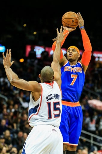 Nov 13, 2013; Atlanta, GA, USA; New York Knicks small forward Carmelo Anthony (7) shoots a three over Atlanta Hawks center Al Horford (15) in the first quarter at Philips Arena. Mandatory Credit: Daniel Shirey-USA TODAY Sports