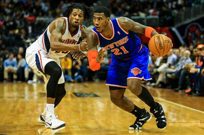Nov 13, 2013; Atlanta, GA, USA; New York Knicks shooting guard Iman Shumpert (21) dribbles past Atlanta Hawks small forward Cartier Martin (20) in the first half at Philips Arena. Mandatory Credit: Daniel Shirey-USA TODAY Sports