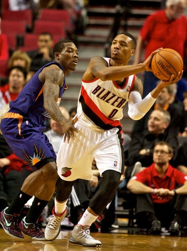 Nov 13, 2013; Portland, OR, USA; Portland Trail Blazers point guard Damian Lillard (0) passes around Phoenix Suns point guard Eric Bledsoe (2) at the Moda Center. Mandatory Credit: Craig Mitchelldyer-USA TODAY Sports
