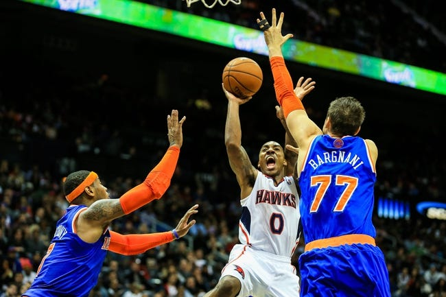 Nov 13, 2013; Atlanta, GA, USA; Atlanta Hawks point guard Jeff Teague (0) shoots through New York Knicks power forward Andrea Bargnani (77) and small forward Carmelo Anthony (7) in the second half at Philips Arena. The Knicks won 95-91. Mandatory Credit: Daniel Shirey-USA TODAY Sports