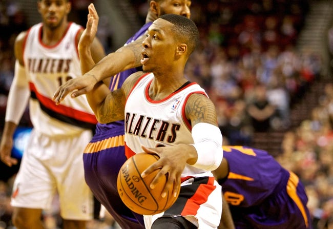 Nov 13, 2013; Portland, OR, USA; Portland Trail Blazers point guard Damian Lillard (0) drives past Phoenix Suns power forward Markieff Morris (11) at the Moda Center. Mandatory Credit: Craig Mitchelldyer-USA TODAY Sports