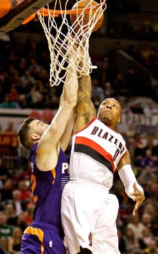 Nov 13, 2013; Portland, OR, USA; Portland Trail Blazers point guard Damian Lillard (0) dunks over Phoenix Suns center Miles Plumlee (22) at the Moda Center. Mandatory Credit: Craig Mitchelldyer-USA TODAY Sports