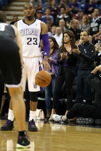 Nov 13, 2013; Sacramento, CA, USA; Sacramento Kings majority owner Vivek Ranadive (right) and daughter Anjali Ranadive (center) stand up and clap as shooting guard Marcus Thornton (23) controls the ball in the final seconds of the game against the Brooklyn Nets during the fourth quarter at Sleep Train Arena. The Sacramento Kings defeated the Brooklyn Nets 107-86. Mandatory Credit: Kelley L Cox-USA TODAY Sports
