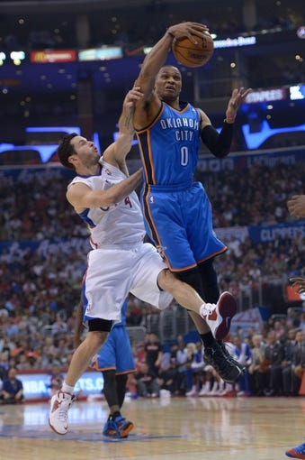 Nov 13, 2013; Los Angeles, CA, USA; Oklahoma City Thunder guard Russell Westbrook (0) and Los Angeles Clippers guard J.J. Redick (4) battle for a rebound at Staples Center. Mandatory Credit: Kirby Lee-USA TODAY Sports