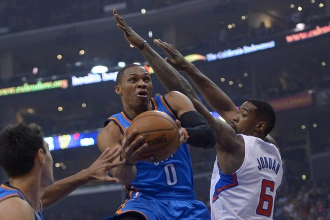 Nov 13, 2013; Los Angeles, CA, USA; Oklahoma City Thunder guard Russell Westbrook (0) is defended by Los Angeles Clippers center DeAndre Jordan (6) at Staples Center. Mandatory Credit: Kirby Lee-USA TODAY Sports
