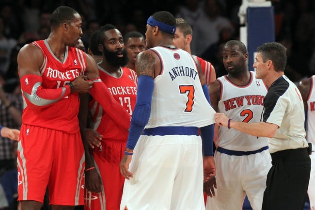 Nov 14, 2013; New York, NY, USA; New York Knicks small forward Carmelo Anthony (7) is restrained by official Scott Foster (48) as he confronts Houston Rockets power forward Dwight Howard (12) and shooting guard James Harden (13) during the third quarter of a game at Madison Square Garden. The Rockets beat the Knicks 109-106. Mandatory Credit: Brad Penner-USA TODAY Sports