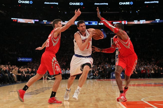 Nov 14, 2013; New York, NY, USA; New York Knicks power forward Andrea Bargnani (77) drives through Houston Rockets small forward Chandler Parsons (25) and Rockets power forward Dwight Howard (12) during the third quarter of a game at Madison Square Garden. The Rockets beat the Knicks 109-106. Mandatory Credit: Brad Penner-USA TODAY Sports