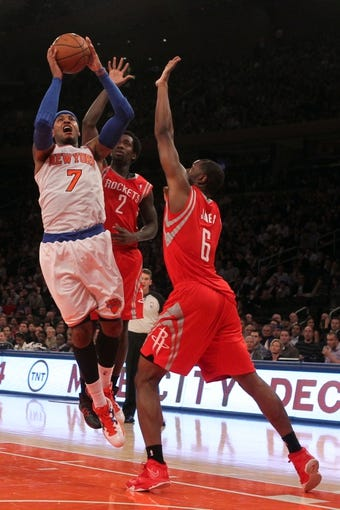 Nov 14, 2013; New York, NY, USA; New York Knicks small forward Carmelo Anthony (7) shoots against Houston Rockets point guard Patrick Beverley (2) and Rockets power forward Terrence Jones (6) during the third quarter of a game at Madison Square Garden. The Rockets beat the Knicks 109-106. Mandatory Credit: Brad Penner-USA TODAY Sports