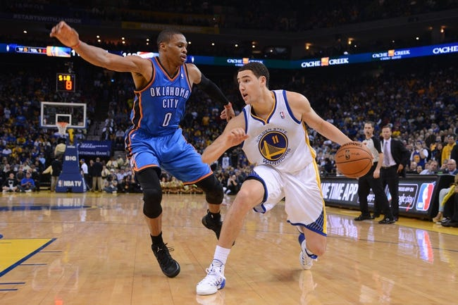 November 14, 2013; Oakland, CA, USA; Golden State Warriors shooting guard Klay Thompson (11) dribbles the ball against Oklahoma City Thunder point guard Russell Westbrook (0) during the fourth quarter at Oracle Arena. The Warriors defeated the Thunder 116-115. Mandatory Credit: Kyle Terada-USA TODAY Sports