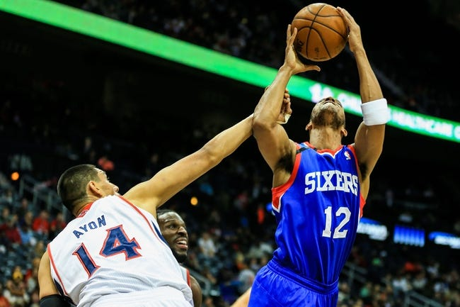 Nov 15, 2013; Atlanta, GA, USA; Philadelphia 76ers small forward Evan Turner (12) is fouled while shooting by Atlanta Hawks power forward Gustavo Ayon (14) in the first quarter at Philips Arena. Mandatory Credit: Daniel Shirey-USA TODAY Sports