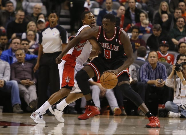 Nov 15, 2013; Toronto, Ontario, CAN; Chicago Bulls forward Luol Deng (9)  drives against Toronto Raptors guard Kyle Lowry (7) during the first half at the Air Canada Centre. Mandatory Credit: John E. Sokolowski-USA TODAY Sports