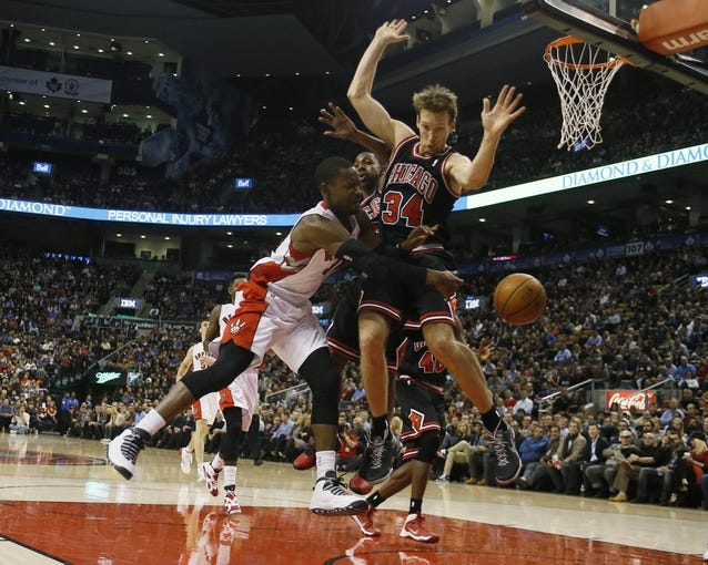 Nov 15, 2013; Toronto, Ontario, CAN; Toronto Raptors guard Terrence Ross (31) passes the ball as Chicago Bulls guard Marquis Teague (25) and Chicago Bulls forward Mike Dunleavy (34) defend during the first half at the Air Canada Centre. Mandatory Credit: John E. Sokolowski-USA TODAY Sports