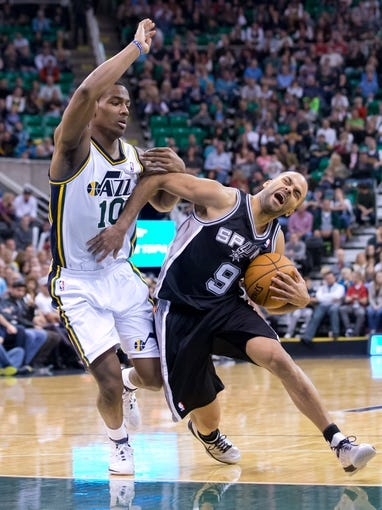 Nov 15, 2013; Salt Lake City, UT, USA; San Antonio Spurs point guard Tony Parker (9) is fouled by Utah Jazz point guard Alec Burks (10) during the second half at EnergySolutions Arena. San Antonio won 91-82. Mandatory Credit: Russ Isabella-USA TODAY Sports