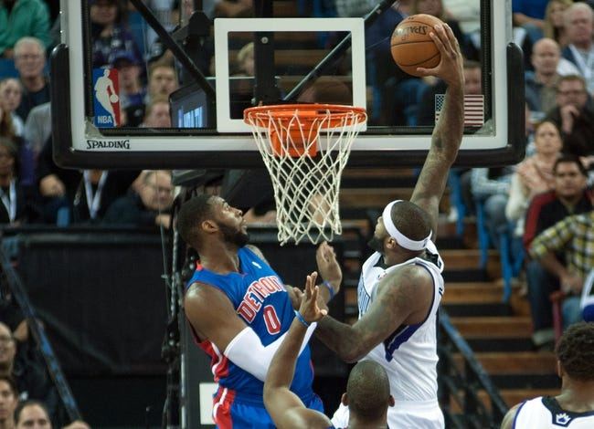 Nov 15, 2013; Sacramento, CA, USA; Sacramento Kings center DeMarcus Cousins (15) dunks the ball over Detroit Pistons center Andre Drummond (0) during the second quarter at Sleep Train Arena. Mandatory Credit: Ed Szczepanski-USA TODAY Sports