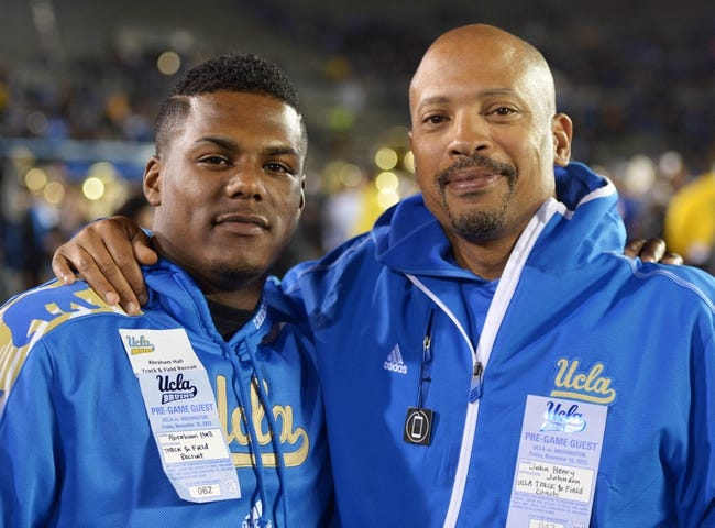 Nov 15, 2013; Pasadena, CA, USA; UCLA Bruins track coach John Henry Johnson (right) poses with Abraham Hall during the game against the Washington Huskies at Rose Bowl.  Mandatory Credit: Kirby Lee-USA TODAY Sports