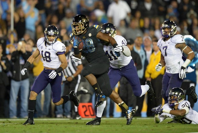 Nov 15, 2013; Pasadena, CA, USA; UCLA Bruins running back Malcolm Jones (28) is pursued by Washington Huskies players Gregory Ducre (18) and Travis Feeney (41) and Shaq Thompson (7) and Kevin King (20) on a 30-yard gain at Rose Bowl. UCLA defeated Washington 41-31.  Mandatory Credit: Kirby Lee-USA TODAY Sports
