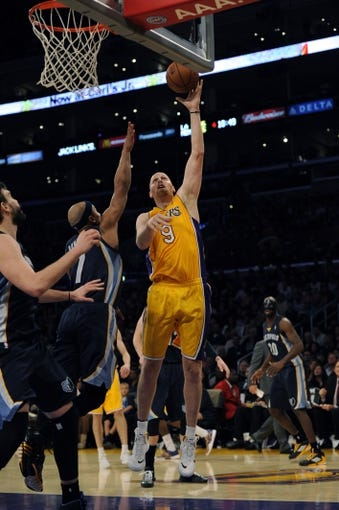 Nov 15, 2013; Los Angeles, CA, USA; Los Angeles Lakers center Chris Kaman (9) goes up for a shot defended by Memphis Grizzlies guard Jerryd Bayless (7) during the fourth quarter at Staples Center. The Memphis Grizzlies defeated the Los Angeles Lakers 89-86. Mandatory Credit: Kelvin Kuo-USA TODAY Sports