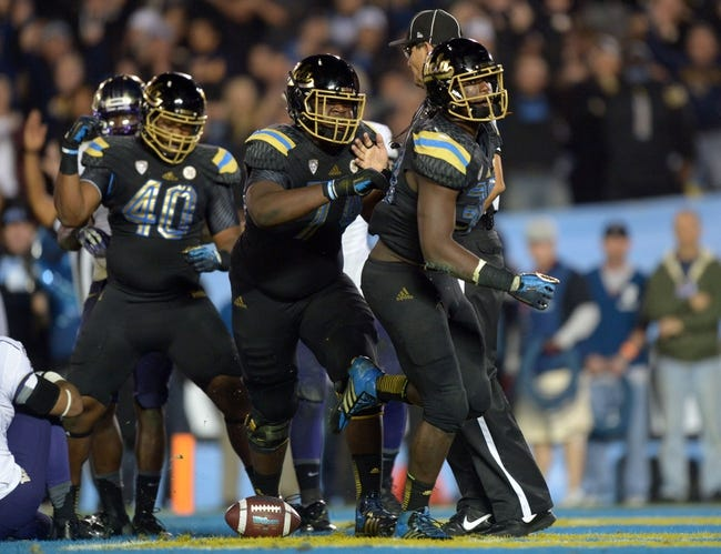 Nov 15, 2013; Pasadena, CA, USA; UCLA Bruins running back Myles Jack (30) celebrates with offensive lineman Caleb Benenoch (74) after scoring on a 2-yard touchdown run in the third quarter for his fourth touchdown against the Washington Huskies at Rose Bowl. Mandatory Credit: Kirby Lee-USA TODAY Sports