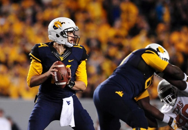Nov 9, 2013; Morgantown, WV, USA; West Virginia Mountaineers quarterback Paul Millard (14) drops back to pass during the game against the Texas Longhorns at Milan Puskar Stadium. Mandatory Credit: Evan Habeeb-USA TODAY Sports