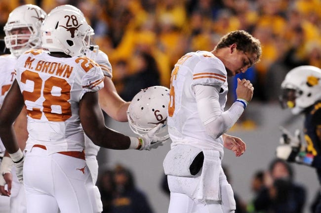 Nov 9, 2013; Morgantown, WV, USA; Texas Longhorns quarterback Case McCoy (6) checks for blood after getting his helmet knocked off during the game against the West Virginia Mountaineers at Milan Puskar Stadium. Mandatory Credit: Evan Habeeb-USA TODAY Sports