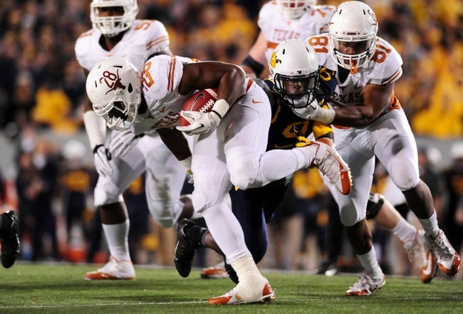 Nov 9, 2013; Morgantown, WV, USA; Texas Longhorns running back Malcolm Brown (28) runs with the ball during the game against the West Virginia Mountaineers at Milan Puskar Stadium. Mandatory Credit: Evan Habeeb-USA TODAY Sports