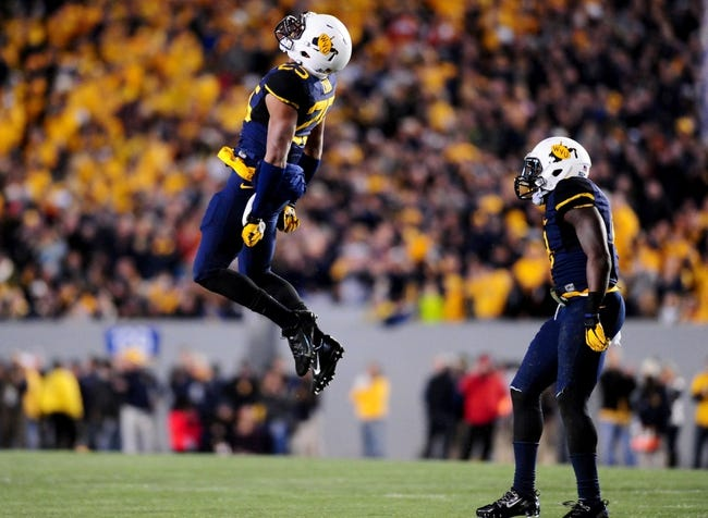 Nov 9, 2013; Morgantown, WV, USA; West Virginia Mountaineers safety Darwin Cook (25) celebrates during the game against the Texas Longhorns at Milan Puskar Stadium. Mandatory Credit: Evan Habeeb-USA TODAY Sports