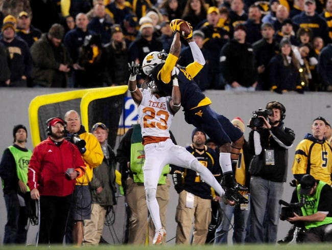 Nov 9, 2013; Morgantown, WV, USA; West Virginia Mountaineers wide receiver Kevin White (11) catches a pass over Texas Longhorns cornerback Carrington Byndom (23) at Milan Puskar Stadium. Mandatory Credit: Evan Habeeb-USA TODAY Sports
